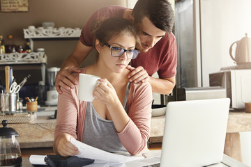Family, debts and financial problems. Frustrated young husband and wife doing paperwork together, calculating their expenses, managing bills, using laptop computer and calculator in modern kitchen