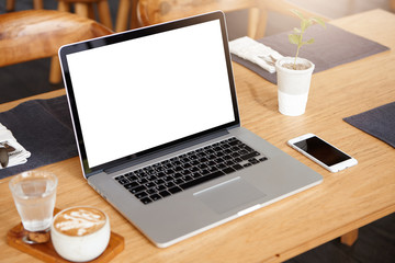 Business, technology and communication concept. Minimalistic workspace with modern laptop computer with white blank screen, generic mobile phone, coffee and glass of water on wooden desk. Mock up