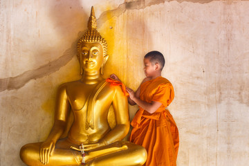 Young novices monk scrubbing buddha statue at temple in thailand