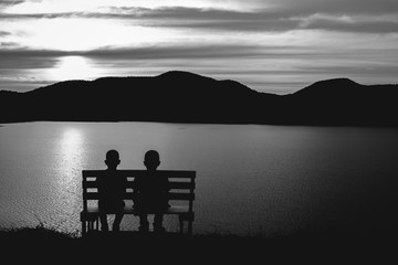 young Asian child, selective focus, vintage, the silhouette of boys sitting looking sunset
