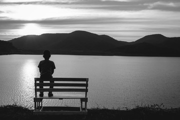 The silhouette of boy sitting alone, concept of lonely, sad, alone, person space, alone and scared