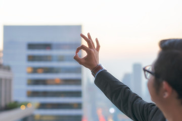OK hand sign showing by businessman with cityscape  on modern building in Business district at Bangkok city background, Symbols concept