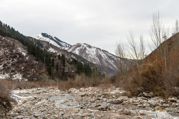 mountain river among large stones in early winter