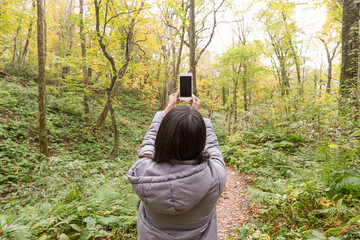 Woman taking photo at forest