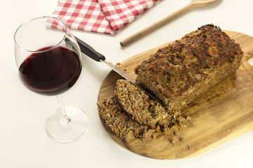 Freshly cooked and cut meatloaf with glass of wine