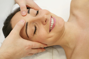 Esthetician massaging head and face of young woman during facial