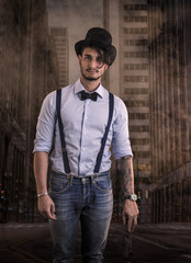 Portrait of brunette young man in glasses, hat, bow-tie, suspenders and shirt on dark smoky city street. Vintage look