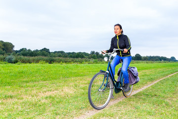 Colombian woman cycling on path in dutch nature landscape