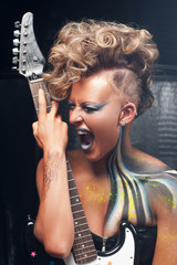 Portrait of aggressive punk with guitar. Stylish woman screaming while performing with guitar, bright rocker look with body art and hairstyle. Subculture, expression, courage, drive, lifestyle concept