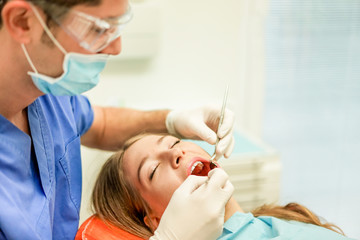 Young woman doing dental treatment - Girl having annual check visit by dentist