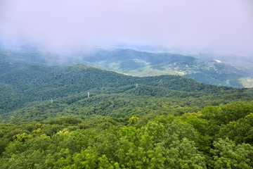 Green hills in valley with low grey clouds and mist
