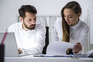 Man and woman looking at clipboard document