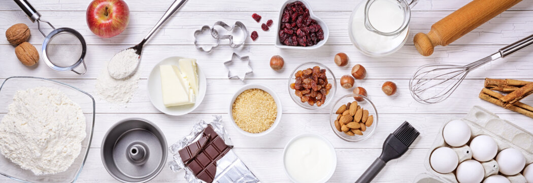 Baking tools and ingredients for cakes on white wooden background. Top view, flat lay.