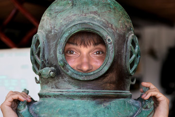 Girl putting on a diving helmet