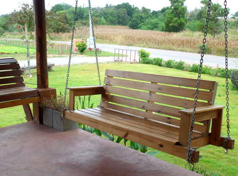 Have Some Rest on a Cozy Wooden Swing at the Terrace