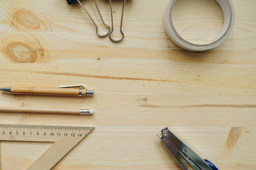 Wood pencil, pen, triangle, briefpapier clips, hefter on the desk in daylight. Office table