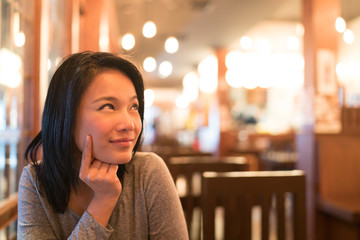 Tanned Asian girl thinking and looking upward to copy space, wondering menu to order for dinner, restaurant advertising concept