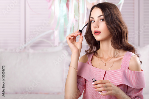 Beautiful woman painting eyelashes free space portrait of beautiful woman painting eyelashes free space portrait of attractive brunette with mascara in pink dress voltagebd Images