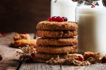 Milk beverages in glass bottles, crisp cookies with pomegranate