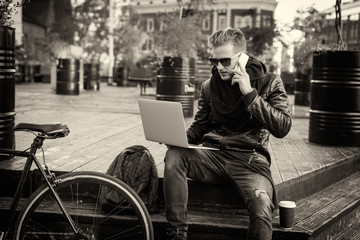 Black and white picture of hipster working on laptop and talking on the phone