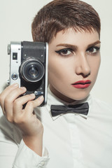 young beautiful photographer woman with short hair style and classic wear with bow tie.  holding camera and looking.