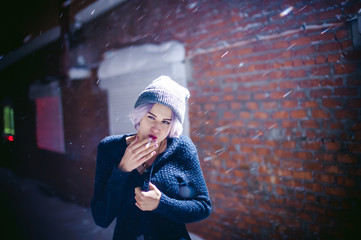 Portrait of a girl with a cigarette. young beautiful girl with dyed hair hipster hat. cigarette smoking on the street under the snow