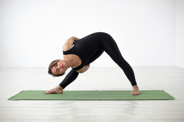 Girl performs a complicated version Utthita Trikonasana on a green mat