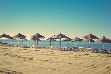 Holiday and vocation image with sandy beach, parasol and chairs on outdoors background