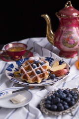 Blueberry apple waffle with honey set on a dish decorated with fresh blueberry, apple, tea pot set ready to serve.