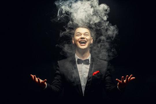 Emotion young Magician playing with Magic smoke
