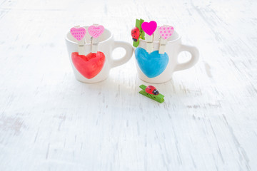 Heart coffee cup and wooden clothes peg on white rustic wooden background, Valentine concept
