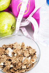 bowl of cereal with fruit, weights and tape measure and concept of diet and healthy living