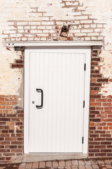 White door surround by old brick work