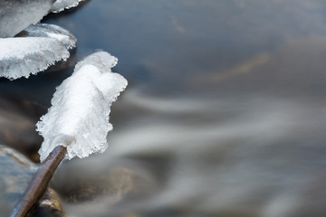 Blurred river water moving under ice formations