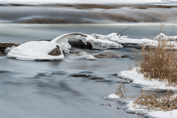 Blurred water moving in river in winter