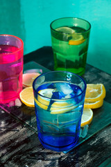 Sparkling water, soda or a gin and tonic in colorful glasses with lemon and ice.Concept for bar menu or detox  with water with lemon.