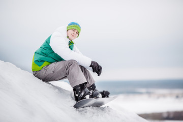 man sitting on the snow with snowboard