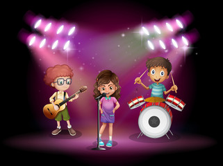 Three kids playing music on stage