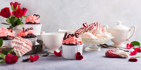 Beautiful chocolate cupcake, pink cream, meringue cookies and red roses on gray stone background. Valentines, Mother Day, wedding concept with with copy space. Banner.