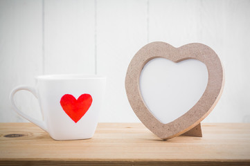 Heart shaped photo frame with cup of love on wood table