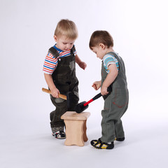 two little boys repairing chair on white