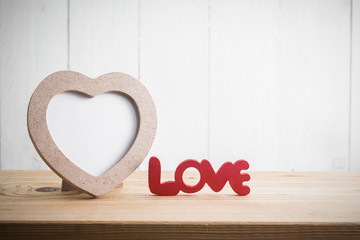 "Heart shaped photo frame with ""Love"" words on wood table"