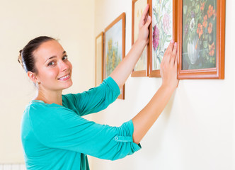 Woman hanging the art picture