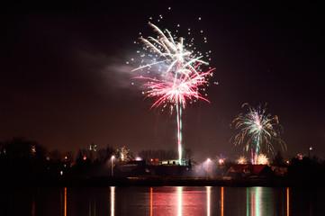 Obraz Sztuczne ognie nad miastem i nad zamarzniętym jeziorem. - fototapety do salonu