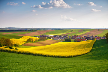 Austria spring colza fields. Village on a hills.