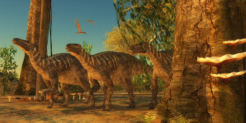 Iguanodons in Forest - Iguanodon dinosaurs make their way among the trees of a Cretaceous forest as Zhejiangopterus reptiles fly over.