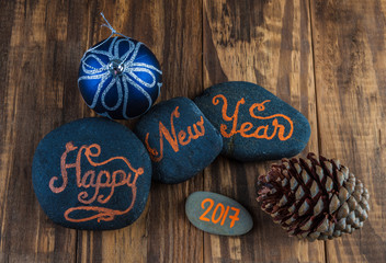 Happy New Year 2017.  Hand lettering written on pebbles.