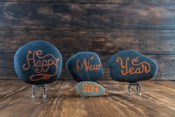 Happy New Year 2017.  Hand lettering written on pebbles placed on tiny chairs on wooden rable