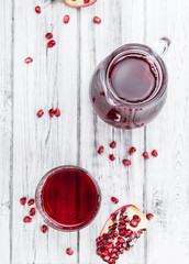 Portion of Pomegranate juice on wooden background (selective foc