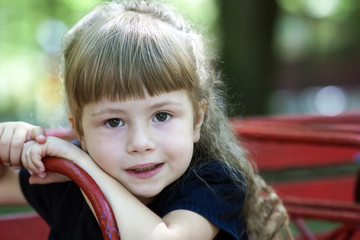 Little girl in an urban setting smiles at the camera. Portrait o